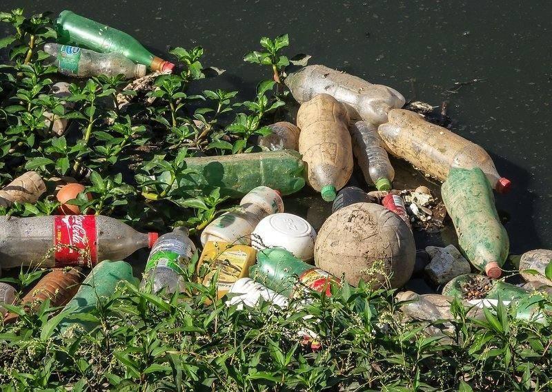 břeh znečištěný plastovými láhvemi a odpadem